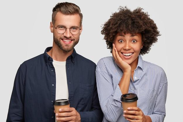 Foto van tevreden gemengd ras vrouw en man houdt wegwerp kopje koffie