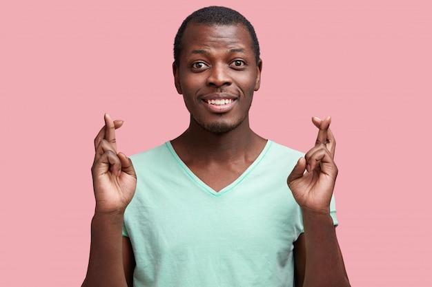 Foto van tevreden jonge afro-amerikaanse man houdt vingers gekruist, nonchalant gekleed, heeft een gelukkige uitdrukking, hoopt op beter of veel geluk, geïsoleerd over roze