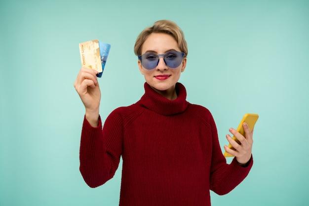 Foto van tevreden jonge vrouw met acneprobleem gezicht huid poseren geïsoleerd op blauwe muur achtergrond met behulp van mobiele telefoon met pinpas.