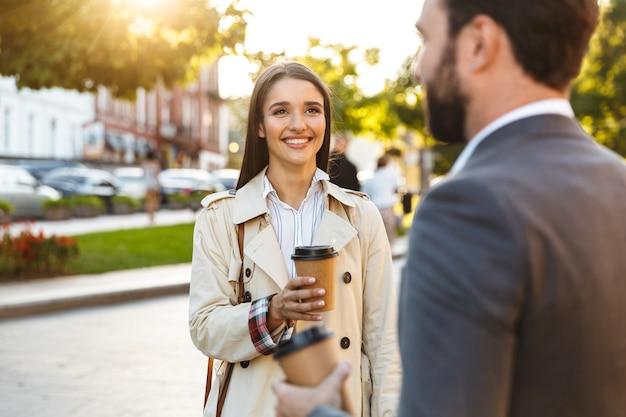 Foto van tevreden kantoormedewerkers, man en vrouw in formele kleding die afhaalkoffie drinken en elkaar aankijken terwijl ze op straat in de stad spreken