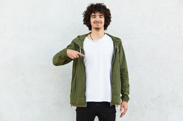 Foto van tevreden lachende hipster heeft baard, krullend haar, geeft met wijsvinger op kopie ruimte van zijn kleding aan, toont plaats voor uw logo, geïsoleerd op witte achtergrond. kijk naar mijn nieuwe outfit