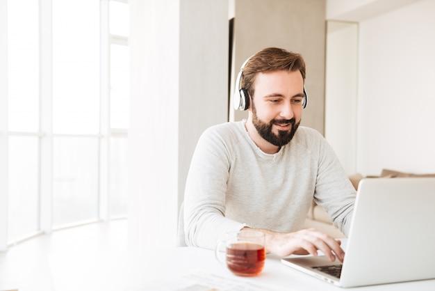 Foto van tevreden man met kort bruin haar en baard die naar muziek luistert via draadloze hoofdtelefoons, terwijl hij aan een laptop werkt