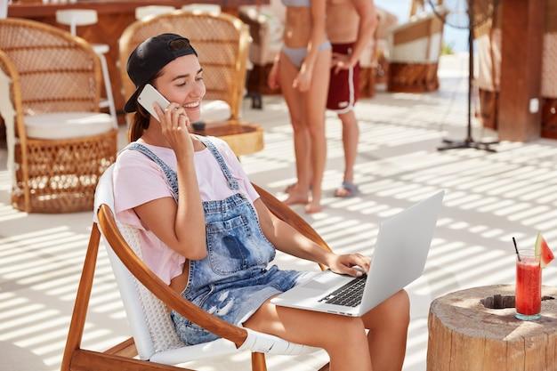 Foto van tevreden modieuze jonge vrouwelijke copywriter recreëert in café in de buurt van het strand, werkt aan het creëren van reclame-inhoud