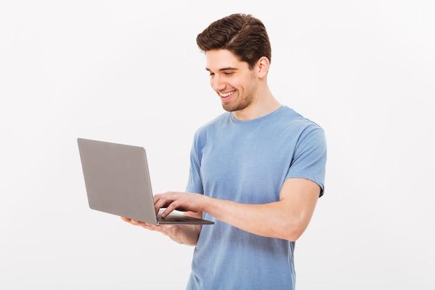 Foto van tevreden ongeschoren man in casual t-shirt met zilveren notebook en chatten of werken, geïsoleerd over witte muur