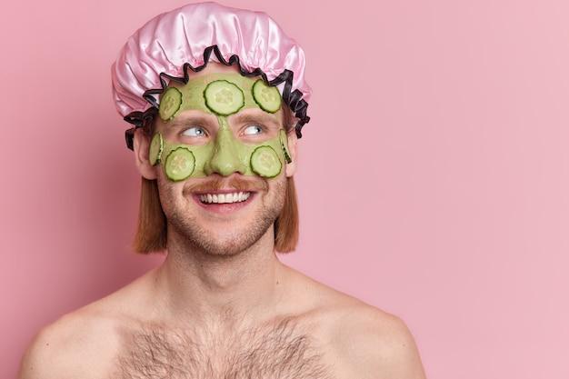 Foto van tevreden ongeschoren man met groen komkommermasker op gezicht ondergaat schoonheidsbehandelingen en geniet van huidverzorgingsroutine