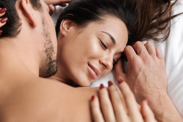 Foto van tevreden paar man en vrouw samen knuffelen, liggend in bed thuis of hotel appartement