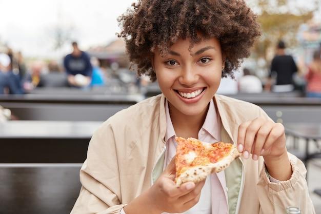 Foto van tevreden tienermeisje met donkere gezonde huid, geniet van heerlijke maaltijd, houdt stuk pizza