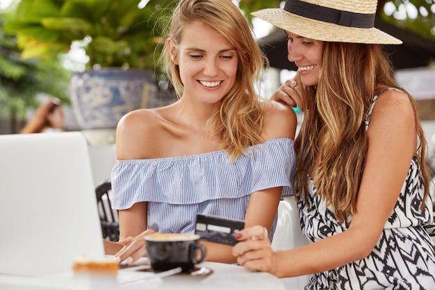 Foto van tevreden twee vrouwtjes in zomerkleding, online aankopen doen met creditcard op laptop, iets kiezen in internetwebwinkel, koffie drinken in restaurant. blije vrouwen genieten van lesiure