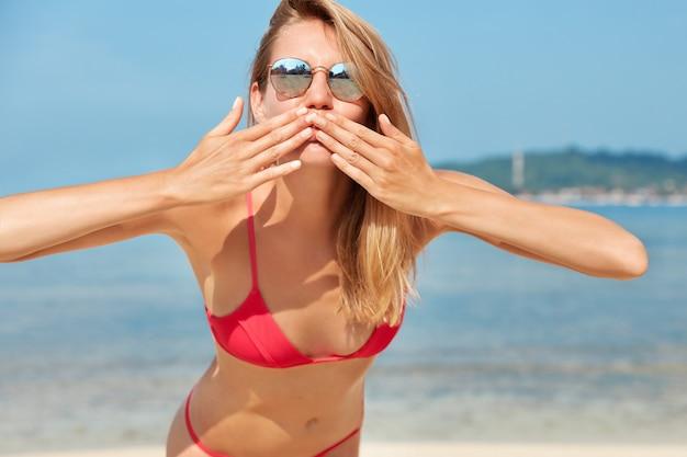 Foto van tevreden vrouwelijke toerist in trendy tinten, blaast luchtkus in de camera, vormt tegen de oceaan tegen de blauwe horizon, heeft een perfect slank lichaam, recreëert aan de kustlijn. mensen, zomer en rust