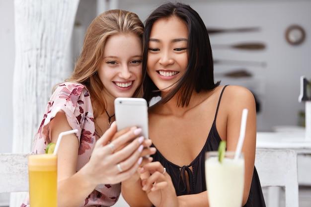 Foto van tevreden vrouwen van gemengd ras krijgen goed nieuws op de mobiele telefoon, ontvangen e-mail of maken een selfie met een smartphone, drinken verse cocktails in de cafetaria.