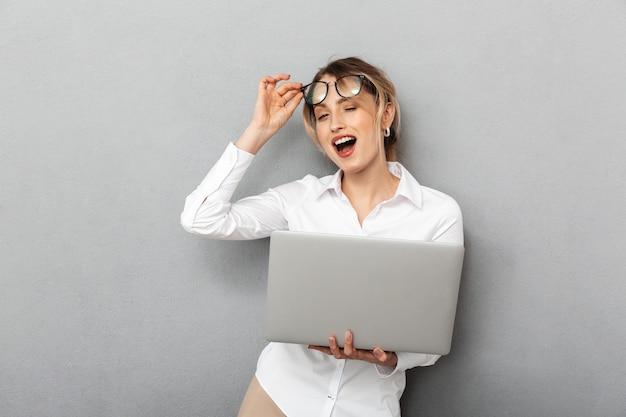 Foto van tevreden zakelijke vrouw die een bril draagt en laptop op kantoor houdt, geïsoleerd