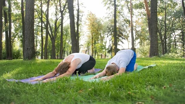 Foto van tiener die yoga doet met zijn moeder op graspark. familie die samen fitness- en rekoefeningen doet in het bos