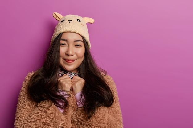 Foto van tienermeisje draagt modieuze hoed en bruine jas, kijkt oprecht met zachte glimlach, geniet van het dragen van nieuwe outfit