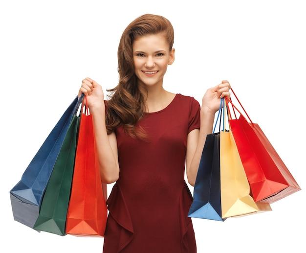 Foto van tienermeisje in rode jurk met boodschappentassen