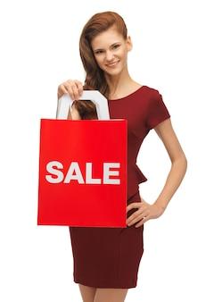 Foto van tienermeisje in rode jurk met verkoopbord