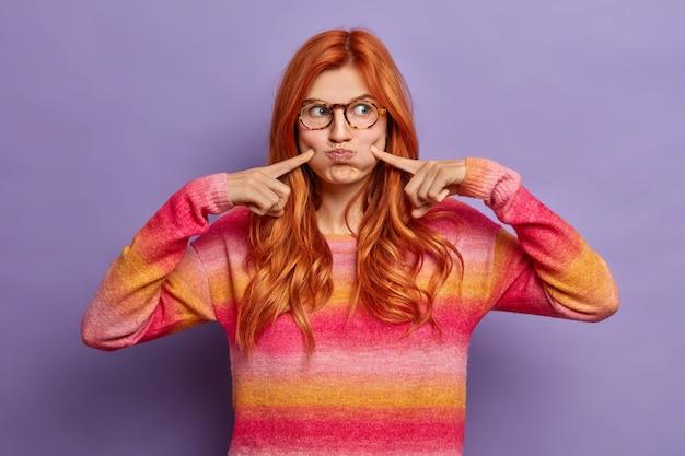 Foto van tienermeisje maakt grappig gezicht expressie klappen wangen en wijst wijsvingers houdt lucht heeft speelse kinderlijke look gekleed in casual jumper dwazen rond.