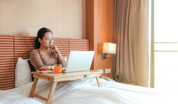 Foto van toeristen die laptop gebruiken en fruit eten op het bed in de luxe hotelkamer, gezond voedselconcept.
