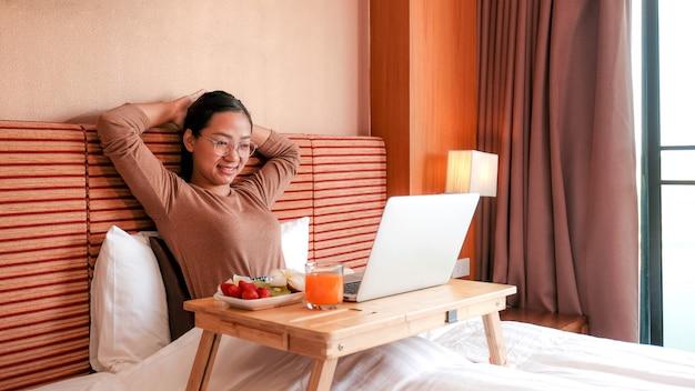 Foto van toeristen die laptop gebruikten en fruit aten op het bed in de luxe hotelkamer