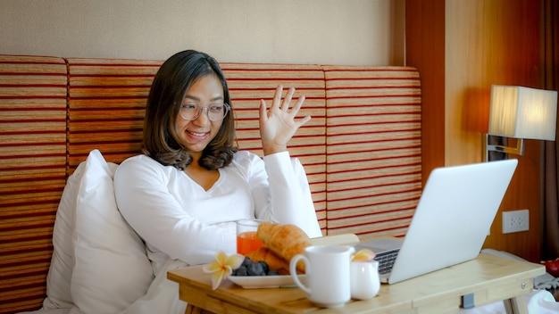 Foto van toeristen die laptop gebruikten en ontbijt aten op het bed in de luxe hotelkamer
