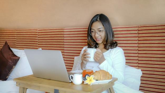 Foto van toeristen die ontbijt eten en laptop gebruikt op het bed in de luxe hotelkamer, gezond voedselconcept.