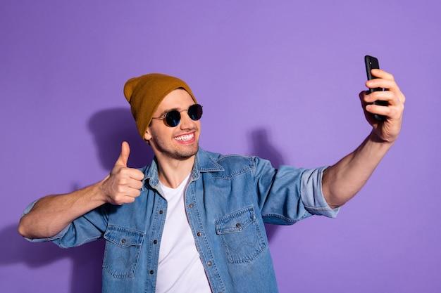 Foto van toothy vrolijke aantrekkelijke jongere blogger positieve feedback geven door videogesprek op telefoon selfie glimlachend stralend weergegeven: duim omhoog geïsoleerd over paarse levendige kleuren achtergrond