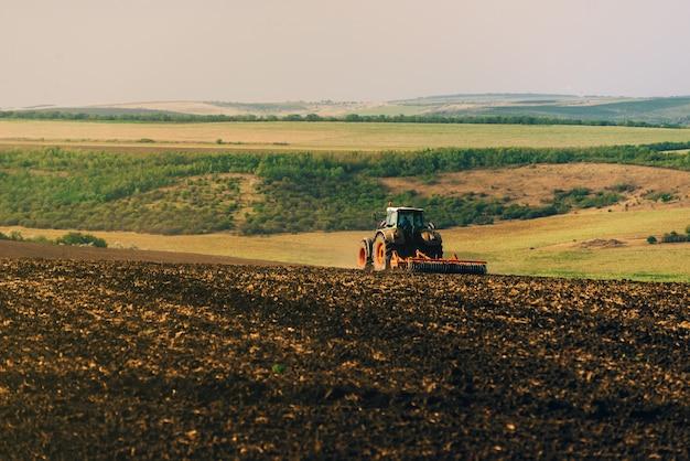 Foto van tractor die een land cultiveert, voorbereiding voor nieuw jaar.