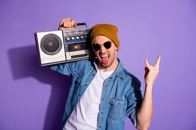 Foto van trendy stijlvolle witte schreeuwende man met retro recorder met handen die je stenen bord tonen schreeuwen met denim t-shirt pet hoofddeksels geïsoleerde paarse felle kleur achtergrond