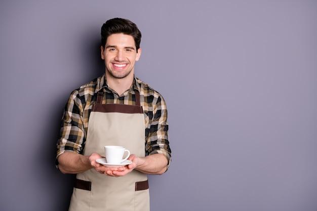 Foto van trendy vrolijke leuke positieve barista die je een kopje thee serveert en strekkende handen geeft om een geïsoleerde grijze kleurmuur te leveren