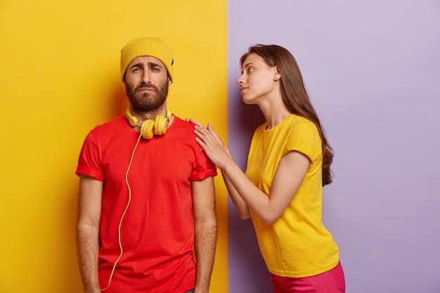 Foto van treurige ongeschoren man heeft problemen, draagt gele hoed en rode t-shirt, grijnst gezicht met ongenoegen, zorgzame vriendin raakt zijn schouder, probeert te kalmeren en te helpen in moeilijke situaties