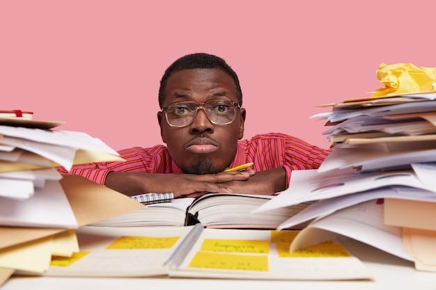 Foto van triest boos donkere huid mannelijke nerd voelt zich eenzaam, heeft geen tijd voor persoonlijk leven, leunt aan bureau, houdt potlood vast, schrijft records op, zit op desktop