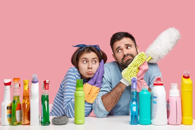 Foto van triest vermoeide vrouw en man hebben ontevreden uitdrukkingen, vermoeidheid na het hele huis schoonmaken tijdens het weekend