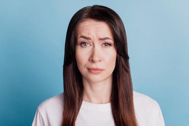 Foto van trieste mensen mooi meisje op zoek geïsoleerd op blauwe achtergrond