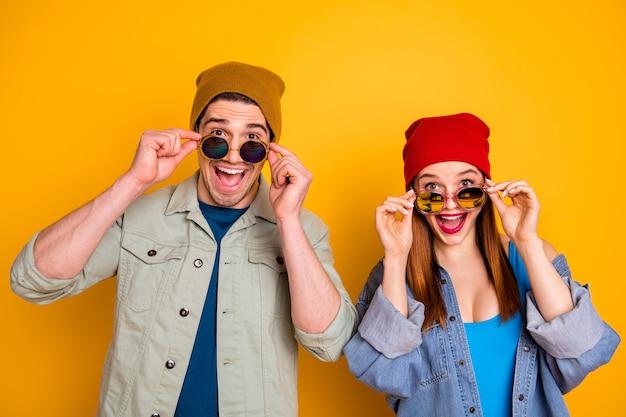 Foto van twee aardige blije positieve verbijsterde mensen die een bril afzetten, geïsoleerde gele zomerachtergrond
