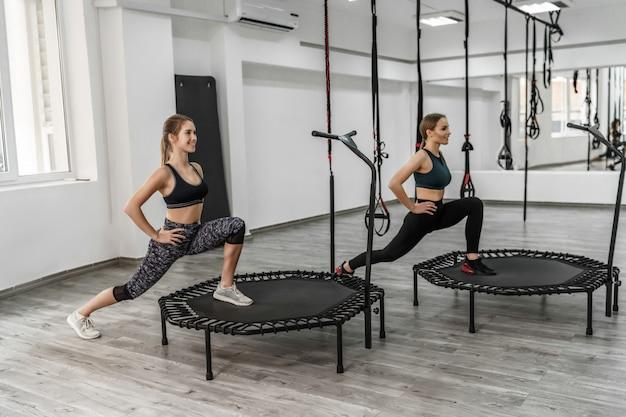 Foto van twee actieve meisjes en fitnesstrainer in sportkleren die oefeningen voor het uitrekken doen
