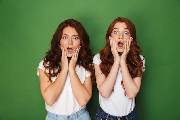 Foto van twee blanke roodharige vrouwen 20s in vrijetijdskleding aanraken van wangen met open mond en uitpuilende ogen, geïsoleerd op groene achtergrond