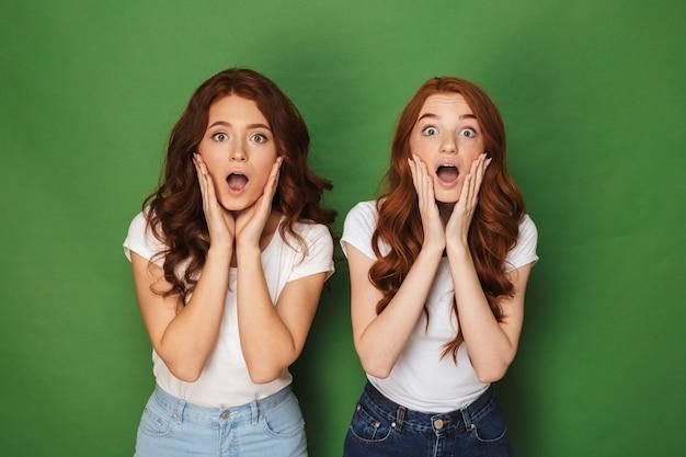 Foto van twee blanke roodharige vrouwen 20s in witte t-shirts aanraken van wangen met open mond en uitpuilende ogen, geïsoleerd op groene achtergrond