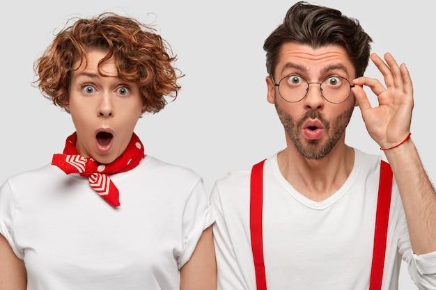 Foto van twee collega's staren verbaasd, monden openhouden van verbazing, dragen stijlvolle kleding. krullend roodharige dame heeft rode bandana staat in de buurt van modieuze man.
