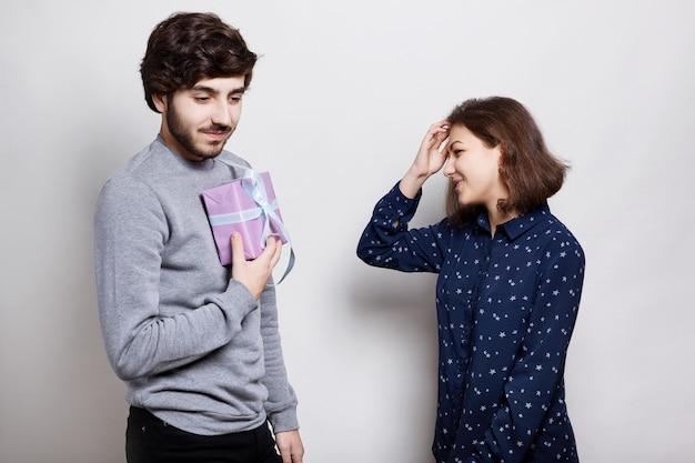Foto van twee echte vrienden. stijlvolle man gaat zijn vriend een cadeau presenteren. gelukkige jonge vrouw die een cadeau gaat ontvangen. jonge hipster met een geschenkdoos in zijn handen.