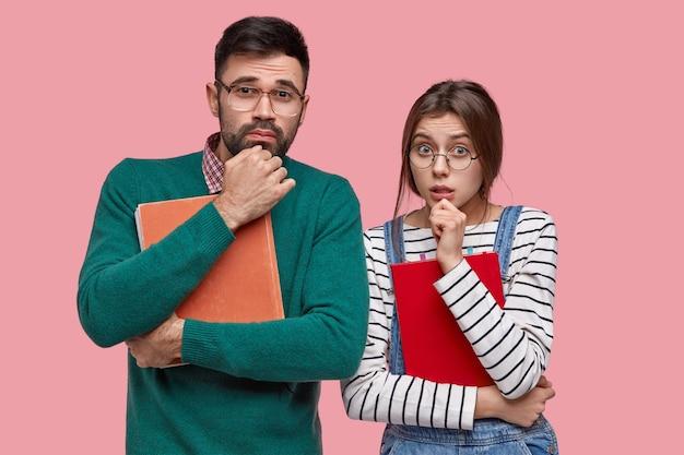 Foto van twee gefrustreerde jonge vrouw en man houden kin vast, kijken aandachtig, dragen encyclopedie en blocnote, bereiden zich voor op seminar