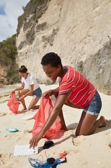 Foto van twee gemengde ras actieve vrouwen zwerfvuil op zandig strand