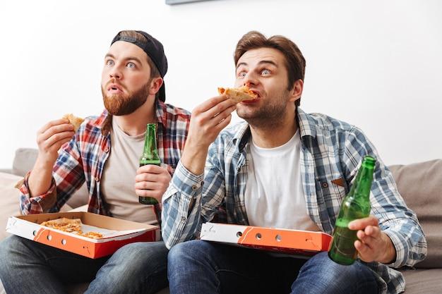 Foto van twee gespannen jongens in casual shirts die pizza eten en bier drinken, terwijl ze thuis aandachtig naar een voetbalwedstrijd kijken