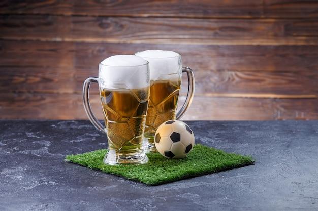 Foto van twee glazen bier, voetbal op groen gras