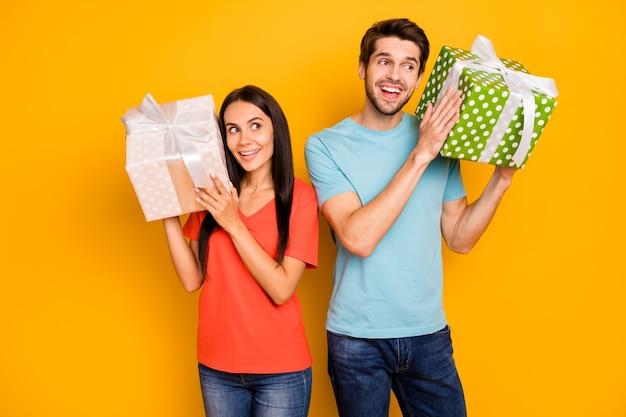 Foto van twee grappige kerel dame mensen hand in hand grote geschenkdozen vroegen zich af om te weten wat erin zit casual trendy blauw oranje t-shirts jeans geïsoleerde gele kleur muur