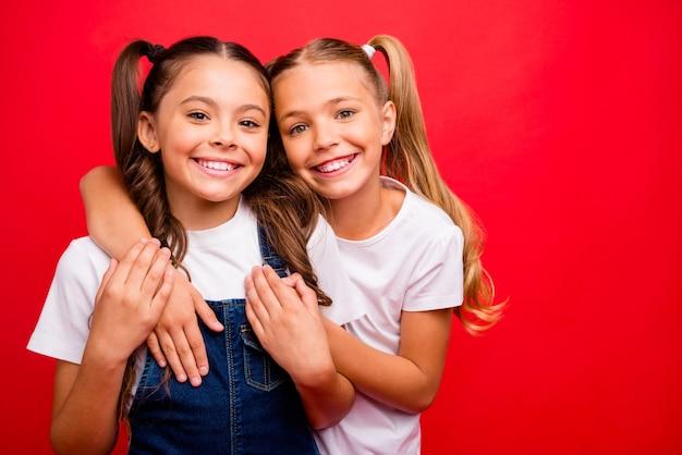 Foto van twee grappige vrij kleine dames knuffelen weekend tijd samen doorbrengen genieten van de beste vakantie dragen jeans overall wit t-shirt geïsoleerde rode kleur achtergrond