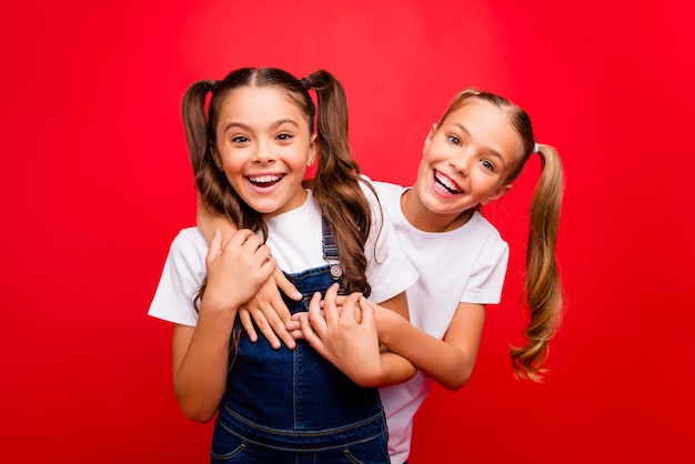 Foto van twee grappige vrij kleine dames weekend tijd samen doorbrengen vrienden genieten van de beste vakantie dragen jeans overall wit t-shirt geïsoleerde rode kleur achtergrond
