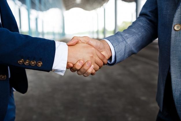 Foto van twee jonge ondernemers op straat handen schudden