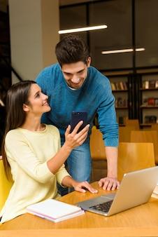 Foto van twee jonge studenten vrienden paar in bibliotheek huiswerk studeren lezen en met behulp van laptop computer en mobiele telefoon.