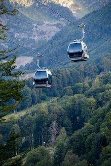 Foto van twee kabelbanen tussen bergheuvels tussen vegetatie