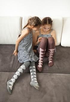 Foto van twee kleine meisjes die op tablet browsen