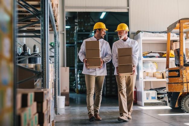 Foto van twee mannelijke magazijnmedewerkers met helmen op hun hoofd die dozen in hun handen dragen. praten en lopen.